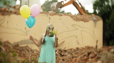savaş : A little girl in a gas mask walks through the ruined buildings with balloons in her hand