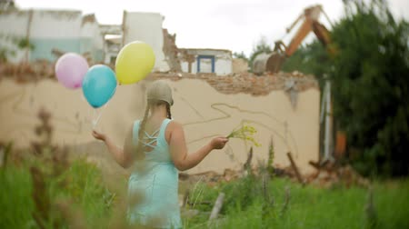 невинный : A little girl in a gas mask walks through the ruined buildings with balloons in her hand