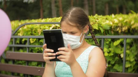 compressor : Cute girl in a respirator uses tablet in the park on a bench
