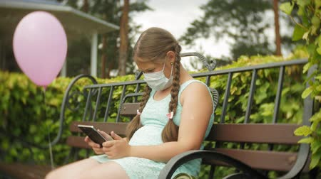 плохо : Cute girl in a respirator uses tablet in the park on a bench
