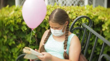 soluma : Cute girl in a respirator reading a book in the park on a bench