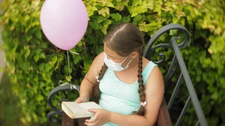 плохо : Cute girl in a respirator reading a book in the park on a bench
