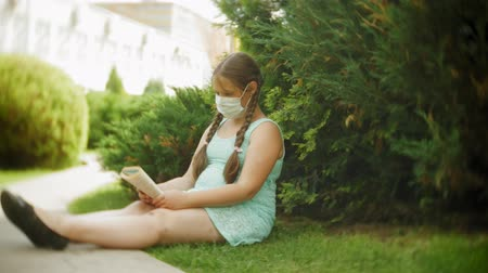 kaszel : Cute girl in a respirator reading a book in the park on a bench