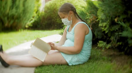 atomizer : Cute girl in a respirator reading a book in the park on a bench