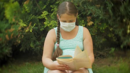 compressor : Cute girl in a respirator reading a book in the park on a bench