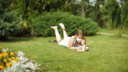 плохо : Cute girl in a respirator reading a book in the park Стоковые видеозаписи