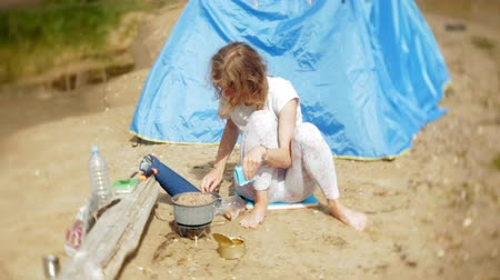 piknik : Women cooking food in bowler in camping with tent on the background. Wideo
