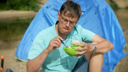 костра : A man is eating around a kettle in a campsite with a tent on the background. Стоковые видеозаписи