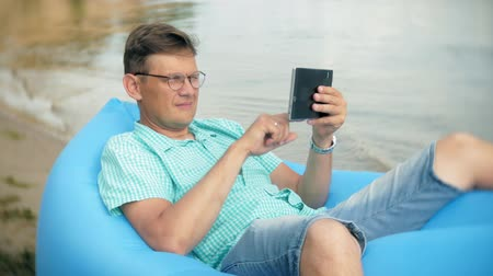 матрац : A man is resting on an inflatable mattress by the sea. He uses a tablet
