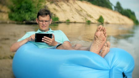 colchão : A man is resting on an inflatable mattress by the sea. He uses a tablet
