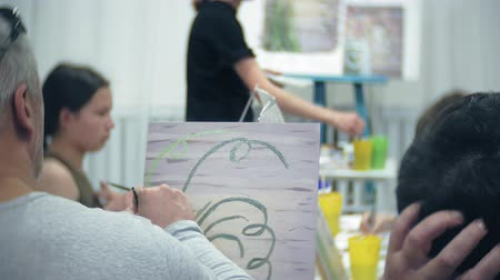 paleta : art school, creativity and people concept - group of students with easels, paintbrushes and palettes painting still life at studio, old and young people draw Dostupné videozáznamy