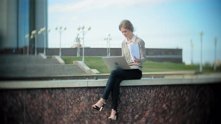 бросать : Young business woman sitting on the steps with a laptop in the business center, reading documents. Стоковые видеозаписи