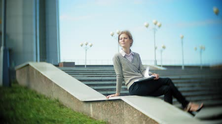 documents : Young business woman sitting on the steps with a laptop in the business center, reading documents. Stock Footage