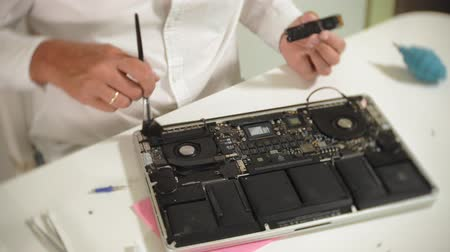 csavarhúzó : A man is repairing a laptop. The concept of computer repair. Close up of man repair laptop motherboard with a screwdriver. Maintenance of the hardware of the motherboard. Disc holder, computer repair of electronic engineer. Stock mozgókép