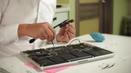 javítás : A man is repairing a laptop. The concept of computer repair. Close up of man repair laptop motherboard with a screwdriver. Maintenance of the hardware of the motherboard. Disc holder, computer repair of electronic engineer. Stock mozgókép