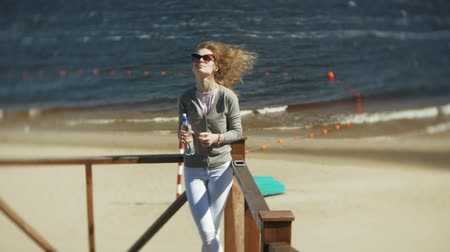 garrafa : Woman drinking water from a bottle on the beach