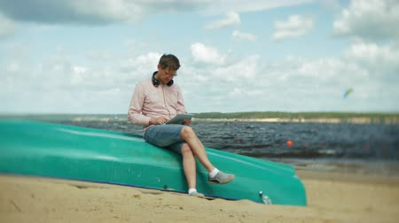 idoso : Old man sits on the beach in headphones near the boat and uses a tablet Stock Footage