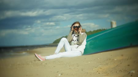 kötelesség : Young woman sits on the beach outside of the boat and looks through binoculars Stock mozgókép