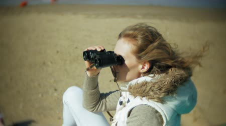 guarda costas : Young woman sits on the beach outside of the boat and looks through binoculars Stock Footage