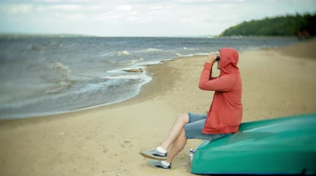 guarda costas : An elderly man sits on the beach outside the boat and looks through binoculars Stock Footage