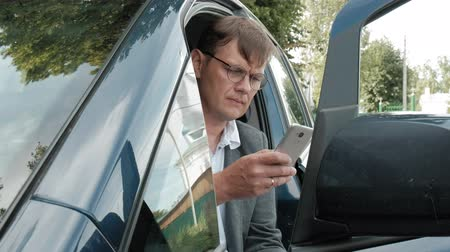 uses : Mature businessman in car uses smartphone