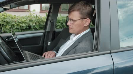 uses : Mature businessman in car working on laptop