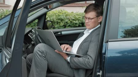 vytočit : Mature businessman in car working on laptop