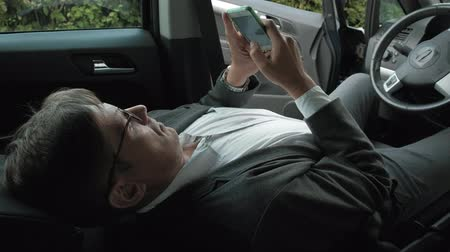 número : Mature businessman in the car lies on the decomposed front seat