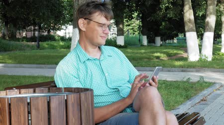 művelt : A man in glasses sits on a bench in the park and uses a phone Stock mozgókép