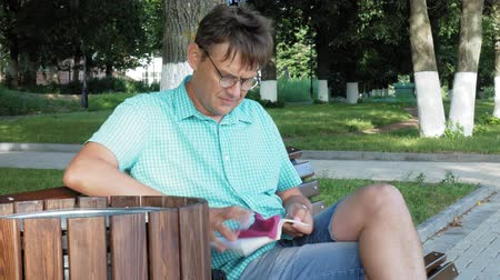 educado : A man in glasses sits on a bench in the park and uses a phone Vídeos