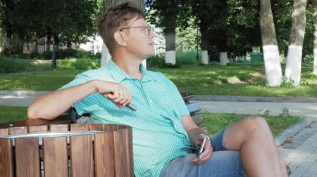 образованный : A man in glasses sits on a bench in the park and uses a phone Стоковые видеозаписи