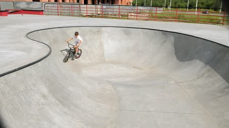bikers : A boy is riding BMX cycling tricks in a skateboard park on a sunny day. Super Slow Motion Stock Footage