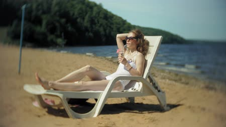 běžný : A young girl in a white bikini lies and sunbathes on a lounger on the sea sandy beach and drinks a cocktail