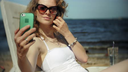 chaise longue : A young girl in a white bikini lies and sunbathes on a lounger on the sea sandy beach and uses smartphone