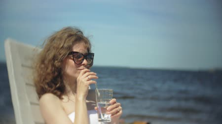 chaise longue : A young girl in a white bikini lies and sunbathes on a lounger on the sea sandy beach and drinks a cocktail