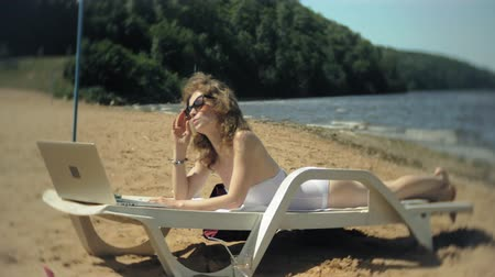 chaise longue : A young girl in a white bikini lies and tans on a deckchair on a sea sandy beach and is working on a laptop