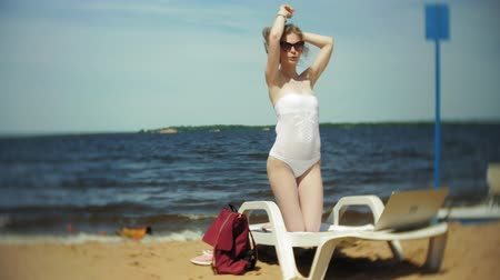 купальный костюм : A young girl in a white bikini lies and tans on a deckchair on a sea sandy beach and is working on a laptop