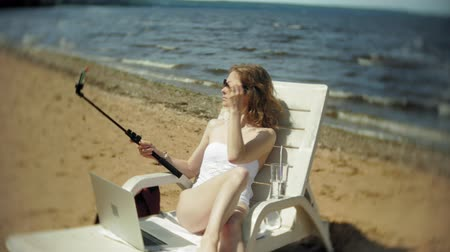 chaise longue : A young girl in a white bikini lies and sunbathes on a deckchair on a sea sandy beach and photographs on a smartphone SELFI Stock Footage
