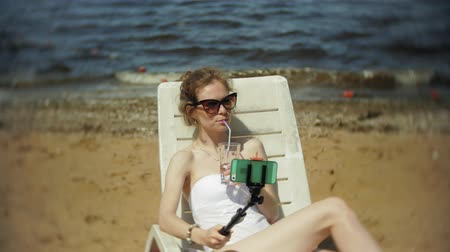 купальный костюм : A young girl in a white bikini lies and sunbathes on a deckchair on a sea sandy beach and photographs on a smartphone SELFI Стоковые видеозаписи
