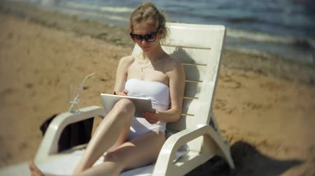 купальный костюм : A young girl in a white bikini lies and tans on a deckchair on a sea sandy beach and is working on a tablet Стоковые видеозаписи
