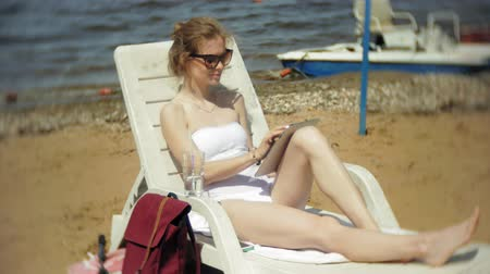 chaise longue : A young girl in a white bikini lies and tans on a deckchair on a sea sandy beach and is working on a tablet Stock Footage