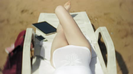купальный костюм : Young girl in white bikini lies and sunbathes on deckchair on sea sandy beach