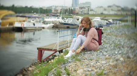 vstup : A girl using a smartphone at seaside,yacht and sailing in the harbour. Dostupné videozáznamy