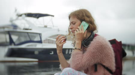 portable information device : A girl using a smartphone at seaside,yacht and sailing in the harbour. Stock Footage