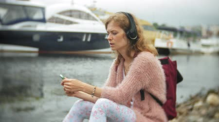 vstup : A girl using a smartphone on the beach, listening to music in headphones, dancing a yacht and sailing in the harbor. Dostupné videozáznamy