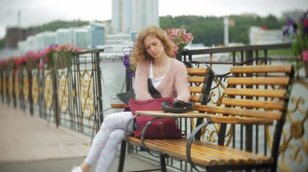 mobile music : A girl using a smartphone on a bench in flowers on the beach, listening to music in headphones, dancing a yacht and sailing in the harbor.