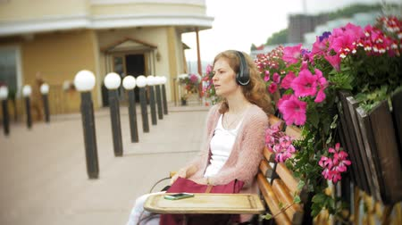 vstup : A girl using a smartphone on a bench in flowers on the beach, listening to music in headphones, dancing a yacht and sailing in the harbor.
