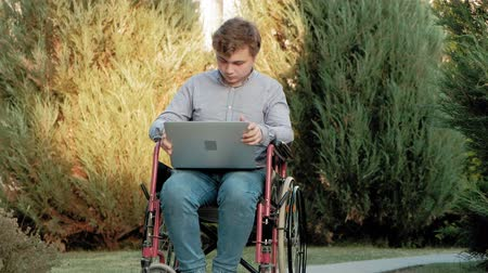 слепой : A disabled man is sitting in a wheelchair and working on a laptop in the park