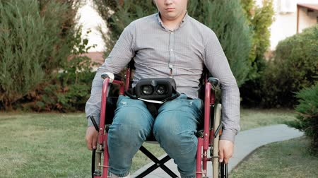 handikap : A disabled man in a wheelchair chair dresses a virtual reality helmet