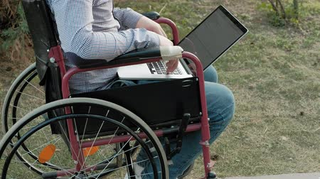 handikap : A disabled man is sitting in a wheelchair and working on a laptop in the park